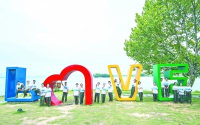 """同学们在东湖绿道鹅咀""""love""""雕塑旁合影 图片来源:长江日报"""