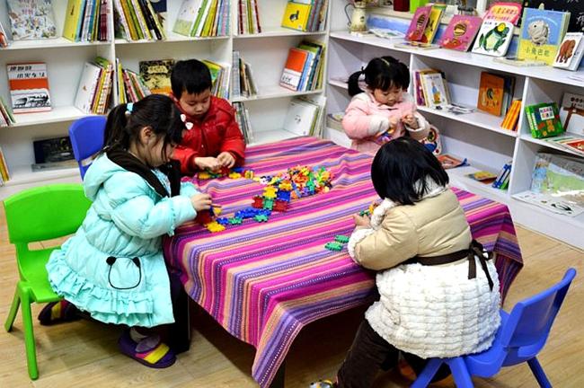 托管班里,小朋友一边玩积木,老师讲故事《长颈鹿不会跳舞》 图片来源图片